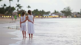 Crianças adoráveis que andam na praia com por do sol colorido bonito video estoque