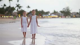 Crianças adoráveis que andam na praia com por do sol colorido bonito filme
