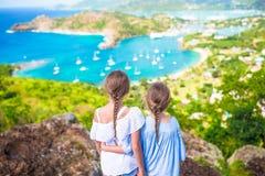 Crianças adoráveis que apreciam a vista do porto inglês pitoresco em Antígua no mar das caraíbas fotografia de stock