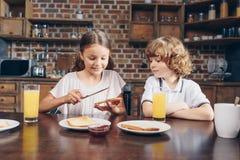 crianças adoráveis que comem o café da manhã foto de stock royalty free
