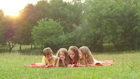Crianças adoráveis que leem um livro em uma tarde agradável do verão do gramado junto Movimento lento video estoque