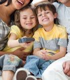 Crianças adoráveis que prestam atenção à tevê com seus pais Fotografia de Stock Royalty Free