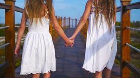 Crianças adoraable pequenas em uma ponte de madeira em sua maneira a um oceano branco da praia e da turquesa video estoque