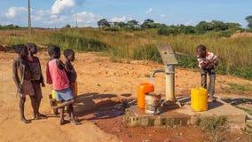 Crianças africanas locais que bombeiam a água potável no construído bem por c Foto de Stock