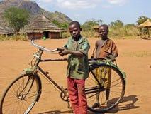Crianças africanas pobres com a vila remota África da bicicleta velha foto de stock