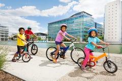 Crianças africanas que apreciam a ciclagem junto na cidade Fotografia de Stock Royalty Free
