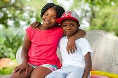 Crianças africanas que sentam-se junto no banco Fotos de Stock Royalty Free
