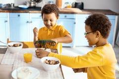 Crianças agradáveis que jogam com dinossauro ao comer o café da manhã foto de stock royalty free