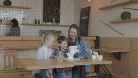 Crianças alegres com a mãe que joga o brinquedo engraçado no café filme