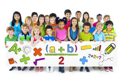 Crianças alegres diversas que guardam símbolos matemáticos fotografia de stock royalty free
