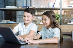 Crianças alegres espertas que usam o portátil junto imagem de stock royalty free