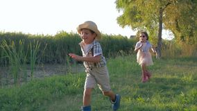 Crianças alegres que correm ao redor fora no campo durante umas férias de verão felizes no luminoso filme