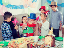 Crianças alegres que dão presentes à menina durante o partido Fotografia de Stock