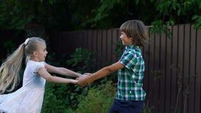 Crianças alegres que guardam as mãos, girando ao dançar, primeiros sentimentos, alegria vídeos de arquivo