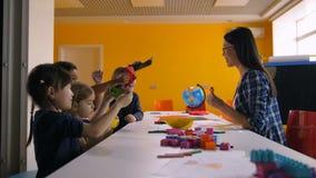 Crianças alegres que jogam com o brinquedo de papel feito a mão video estoque