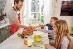 Crianças alegres que têm o divertimento com pai durante o café da manhã imagens de stock