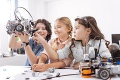 Crianças alegres que testam o dispositivo moderno na escola Fotografia de Stock
