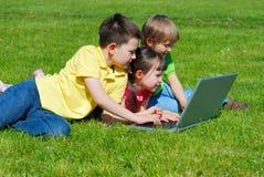 Crianças ao ar livre com computador Fotos de Stock Royalty Free