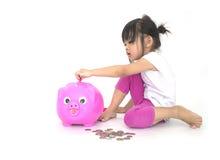 Crianças asiáticas com mealheiro cor-de-rosa Fotos de Stock Royalty Free