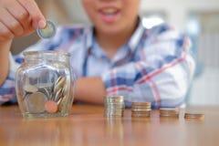 crianças asiáticas da criança do menino da criança com o frasco da pilha das moedas Economias do dinheiro fotos de stock royalty free