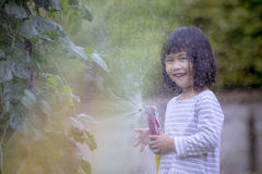 Crianças asiáticas que jogam a água que espirra o frome uma mangueira com o happine Imagens de Stock Royalty Free