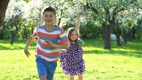 Crianças ativas menino e corrida da menina longe do balanço no jardim de florescência da mola vídeos de arquivo
