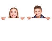 Crianças atrás de uma placa branca Imagens de Stock Royalty Free