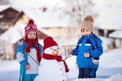 Crianças bonitas felizes, irmãos, boneco de neve de construção no jardim, Fotos de Stock Royalty Free