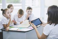 Crianças bonitas, os estudantes e professor junto em uma classe fotos de stock