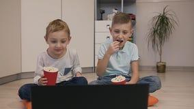 Crianças bonitas que sentam-se no assoalho em descansos alaranjados na sala branca que olha um filme e comer engraçados delicioso filme