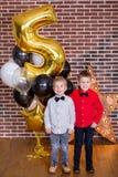 Crianças bonitas, rapazes pequenos que comemoram o aniversário e que fundem velas no bolo cozido caseiro, interno Festa de anos p Imagens de Stock
