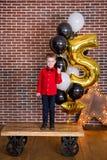 Crianças bonitas, rapazes pequenos que comemoram o aniversário e que fundem velas no bolo cozido caseiro, interno Festa de anos p Imagem de Stock