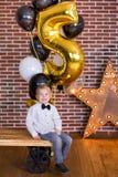 Crianças bonitas, rapazes pequenos que comemoram o aniversário e que fundem velas no bolo cozido caseiro, interno Festa de anos p Foto de Stock Royalty Free