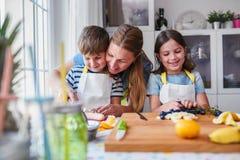 Crianças bonitos com a mãe que prepara um petisco saudável do fruto na cozinha Foto de Stock Royalty Free