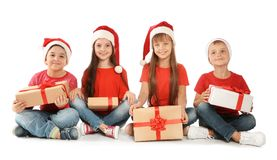 Crianças bonitos em chapéus de Santa com os presentes do Natal no fundo branco Fotos de Stock Royalty Free