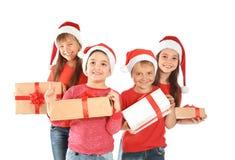 Crianças bonitos em chapéus de Santa com os presentes do Natal no fundo branco Fotografia de Stock Royalty Free
