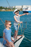 Crianças bonitos felizes a bordo do iate luxuoso no dia ensolarado do verão no porto Foto de Stock