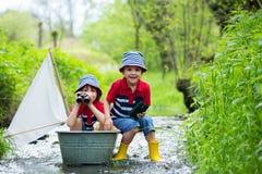 Crianças bonitos, meninos, jogando com barco e patos em pouco riv Fotografia de Stock