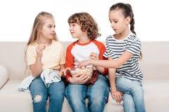 Crianças bonitos no sofá com pipoca imagem de stock