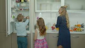 Crianças bonitos que ajudam a mãe a fazer em casa o café da manhã vídeos de arquivo