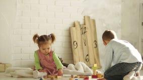 Crianças bonitos que aprendem empilhar junto blocos do brinquedo O irmão corre afastado video estoque