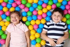 Crianças bonitos que encontram-se no assoalho perto das bolas coloridas, vista superior imagem de stock royalty free