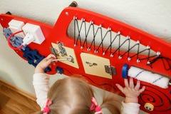 Crianças bonitos que jogam com placa ocupada no jardim de infância fotografia de stock