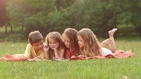 Crianças bonitos que leem um livro no verão do jardim junto um o bom dia Movimento lento Fim acima vídeos de arquivo