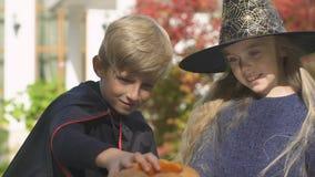Crianças bonitos que preparam-se para o partido de Dia das Bruxas, cinzelando a lanterna da abóbora, família vídeos de arquivo