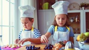 Crianças bonitos que preparam uma salada de fruto na cozinha Fotografia de Stock