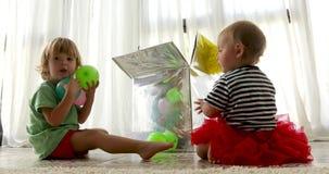Crianças bonitos que sentam-se no assoalho e que jogam com balões coloridos filme