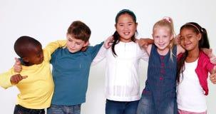 Crianças bonitos que sorriem na câmera e que mostram os polegares acima filme