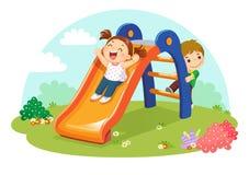 Crianças bonitos que têm o divertimento na corrediça no campo de jogos ilustração stock