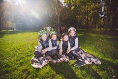 Crianças caucasianos da grande família Três irmãos e descanso de assento da irmã na cobertura fora do parque Grama verde do  imagem de stock